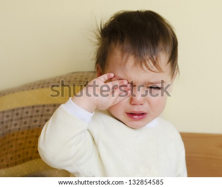 Sleepy toddler child crying in a bed after waking up or before going to sleep. - stock photo