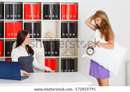 Sleepy woman in a nightgown with alarm clock in a hand stands in the office of the the chief. Being late for work. - stock photo