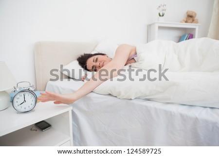 Sleepy woman in bed extending hand to alarm clock - stock photo