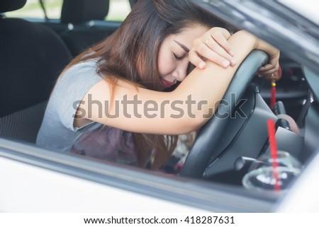 Sleepy woman sitting in car - stock photo