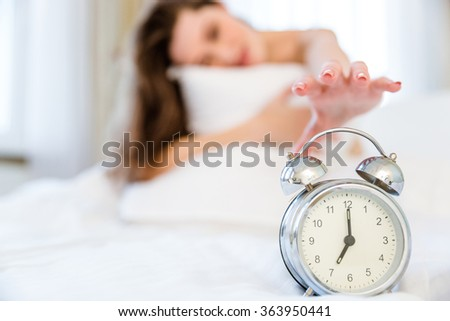 Sleepy woman trying to turn off the alarm clock. Focus on alarm