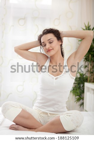 sleepy woman waking up and yawning with a stretch while sitting in bed - stock photo