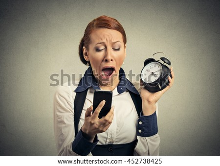 Sleepy woman with mobile smart phone and alarm clock isolated on gray wall background  - stock photo