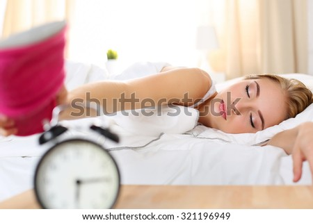 Sleepy young beautiful woman trying kill alarm clock with pink slipper. Early wake up, not getting enough sleep, getting work concept. Female stretching hand to ringing alarm willing turn it off - stock photo
