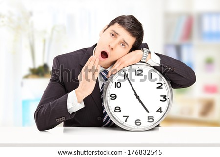 Sleepy young businessman leaning his head on a big wall clock, indoors - stock photo