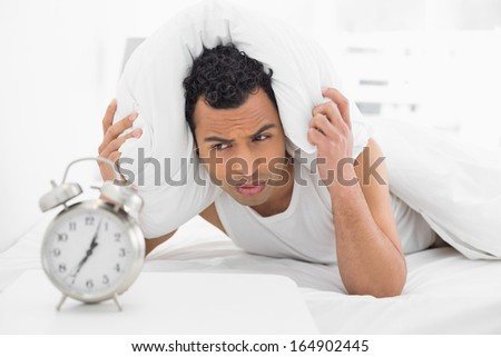 Sleepy young man covering ears with pillow as he looks at alarm clock in bed - stock photo