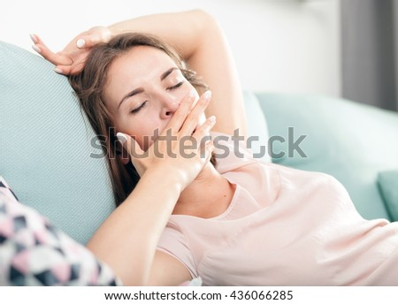Sleepy young woman lying on couch and relaxing at home, casual style indoor shoot - stock photo