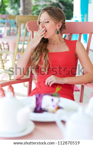 sleepy young woman sitting in the cafe and yawning - stock photo