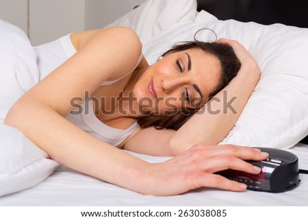 sleepy young woman switching off the alarm clock.  - stock photo