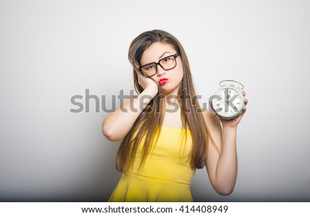 Sleepy young woman with a retro alarm clock in yellow clothes close-up isolated
