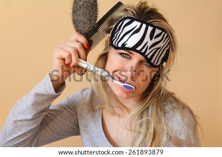 Sleepy young women brushing her teeth and hair at the same time with the sleeping eye mask still on. - stock photo