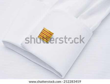 Sleeve of a white shirt with a yellow cuff link - stock photo