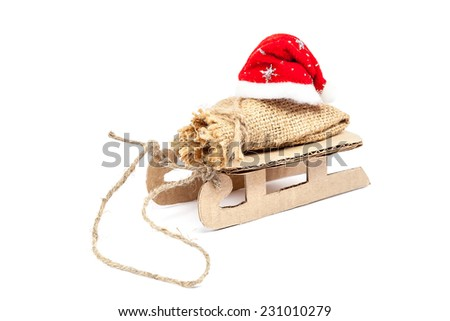 Sleigh with a sack and a Santa Claus hat isolated on white background. - stock photo
