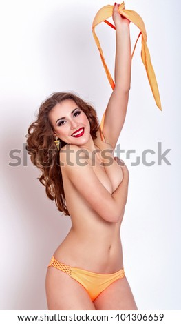 Slender attractive girl measures the swimsuit in a store. Girl holding a bra on a bathing suit, hiding her breasts. Shopping. Preparation for the beach season. - stock photo