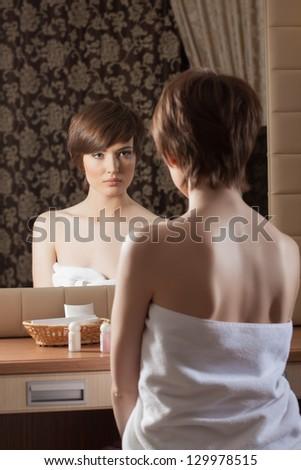 Slender brunette in towel posing near mirror - stock photo