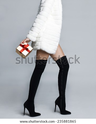 Slender female in elegant boots stockings with gift - stock photo