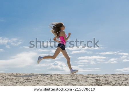 Slender girl in a pink T-shirt is engaged in jogging on  beach - stock photo