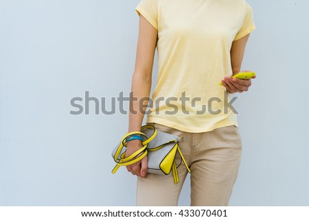 Slender girl in a yellow T-shirt holding yellow lady's handbag and mobile phone - stock photo
