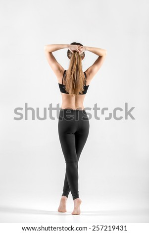 Slender girl standing on tiptoes holding her hair in arms. Sporty, healthy lifestyle, healthcare, fitness, weight loss concepts - stock photo