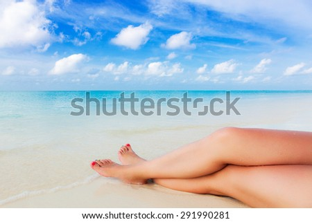 slender tanned legs of a young girl on the beach turquoise waters of the Caribbean Ocean in the Maldives, the Bahamas Hawaii - stock photo