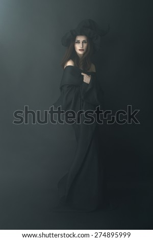 slender witch in a dark fog is beautiful - stock photo