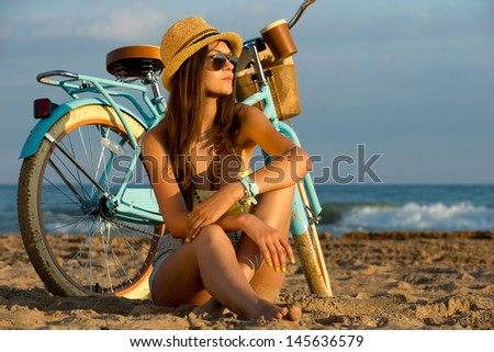 slender young brunette girl posing with a vintage bicycle on a background of the sea - stock photo
