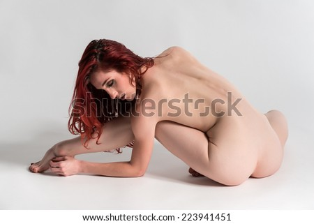 Slender young redhead nude on white - stock photo