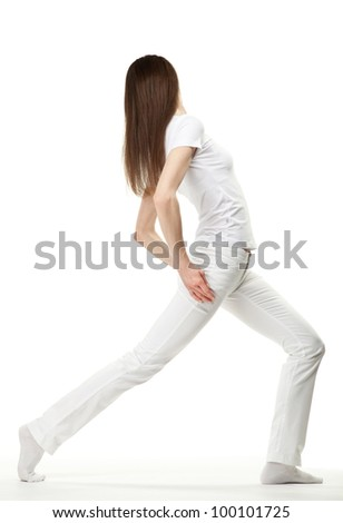 Slender young woman doing sport exercises or dancing on white background