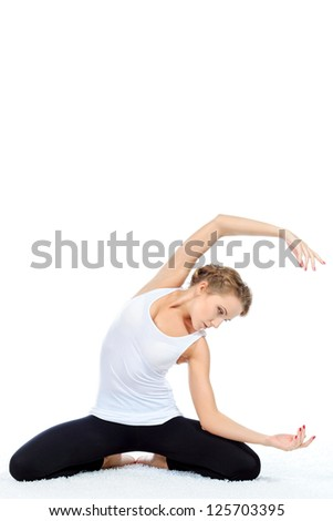 Slender young woman doing yoga exercise. Isolated over white background. - stock photo