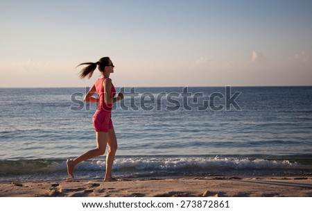 Slender young woman running along the coast - stock photo