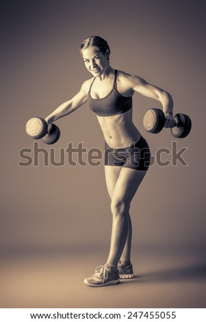 Slender young woman with beautiful athletic body doing exercises with dumbbells. Fitness, bodybuilding. Health care. Black-and-white photo. - stock photo