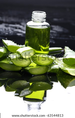 slice aloe with bowl of aloe lotion- Spa still life - stock photo