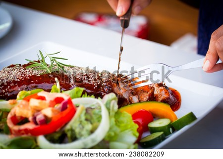 Slice BBQ Ribs - Marinated pork ribs with salad, french fries and barbecue sauce. - stock photo