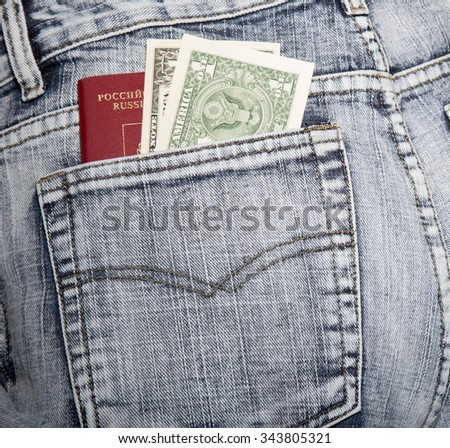 Slice of a cover of the Russian passport and two notes on one dollar in a hip-pocket of blue jeans - stock photo