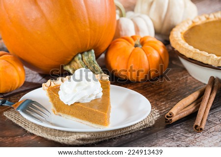 Slice of a pumpkin pie and pumpkins on wooden table - stock photo