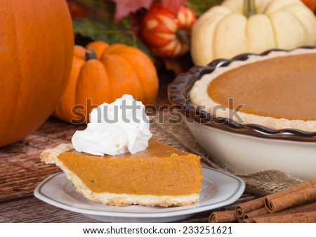 Slice of a pumpkin pie with whipped cream on wooden table. Pie and pumpkins on the background. - stock photo