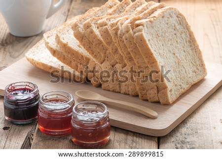 Slice of a whole wheat bread with small jam jar
