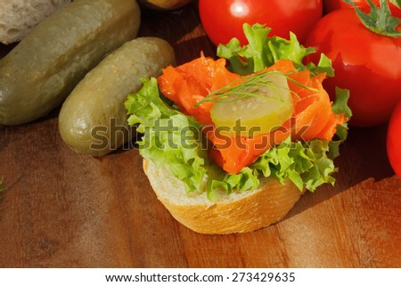 Slice of baguette with pollock fillet, garnished with lettuce, onion, tomato and pickles on a wooden board - stock photo