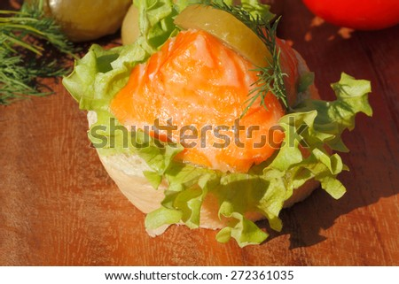 Slice of baguette with smoked salmon filet, garnished with lettuce, onion, tomato and pickles on a wooden board - stock photo