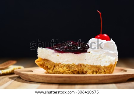 slice of blueberry cheese cake with cherries on wooden table - stock photo