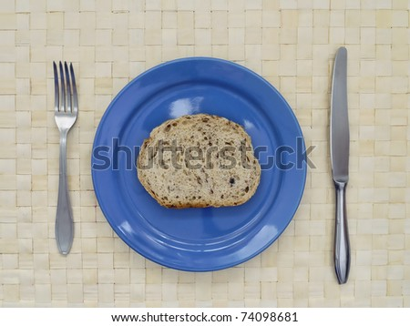 Slice of bread on blue plate with fork and knife - stock photo