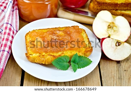 Slice of bread with apple jam and mint on a plate, a jar of marmalade, a napkin on the background of wooden boards - stock photo
