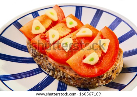 slice of bread with butter, tomato and garlic at plate - stock photo