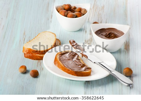 Slice of bread with chocolate cream on blue wooden background - stock photo