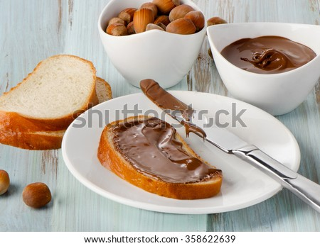 Slice of bread with chocolate cream on wooden background - stock photo