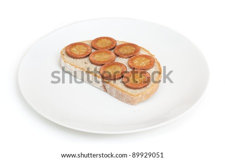 Slice of bread with coins put like a salami, lying on plate isolated on white background. - stock photo