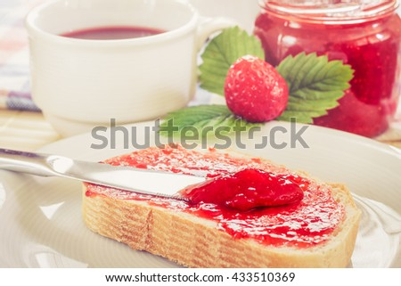 Slice of bread with jar of strawberry jam, tea in teacup, and fresh strawberries and leaves next to it. Concept image for breakfast - stock photo
