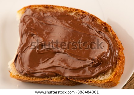Slice of bread with sweet chocolate nougat spread on white plate. - stock photo