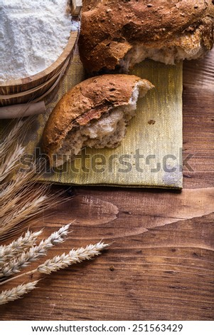 slice of bread with wheat ears and flour in bucket on old wooden board  - stock photo