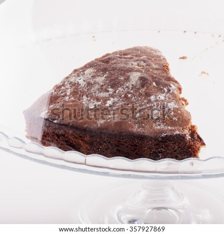 Slice of cake in a glass stand, square image